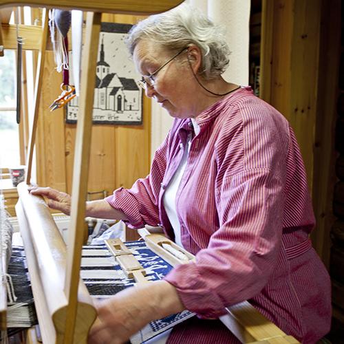 Gerd Kolstad har vært ansatt ved Grinakervev siden starten. Her vever hun på et veggteppe.