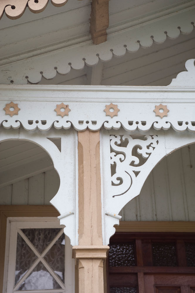 Detalj fra sveitserhus med flotte løvsagarbeider og tidstypisk fargesetting.