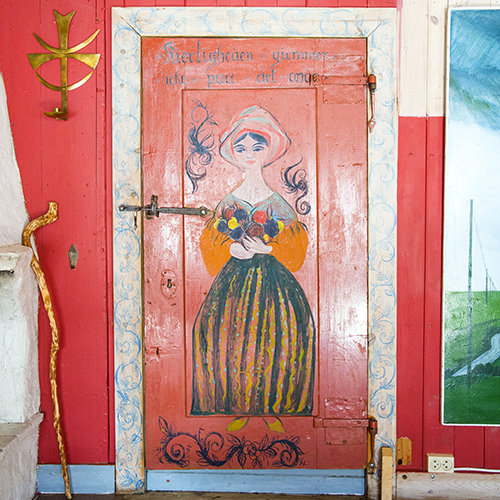 Ela forvandlet Thomasgården til et kunstverk. Hennes fargerike og livlige dekor er nesten overalt. På bildet ses motivet «Kiærligheten giemmer icke paa det onde»