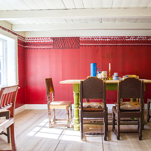 Kjøkkenet/eldhuset med grua, en kopi av en lokal peis, og et stort matskap som skjulte kjøleskapet. Skifergulvet er lagt av Ela og Henry.Det første besøkende møter er Elas naivistiske «kroting» i svart og hvitt.