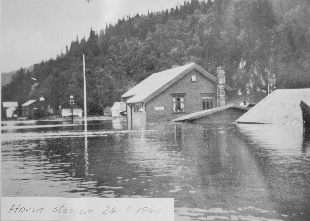 På det gamle bildet ses stasjons-bygningen under den store flommen 29. august 1940. Da sto vannet godt over etasjeskillet på butikken og det var en krevende oppryd-ningsprosess. Men husene står her den dag i dag. Det sier vel litt om kvaliteten på trevirket de er bygget i.