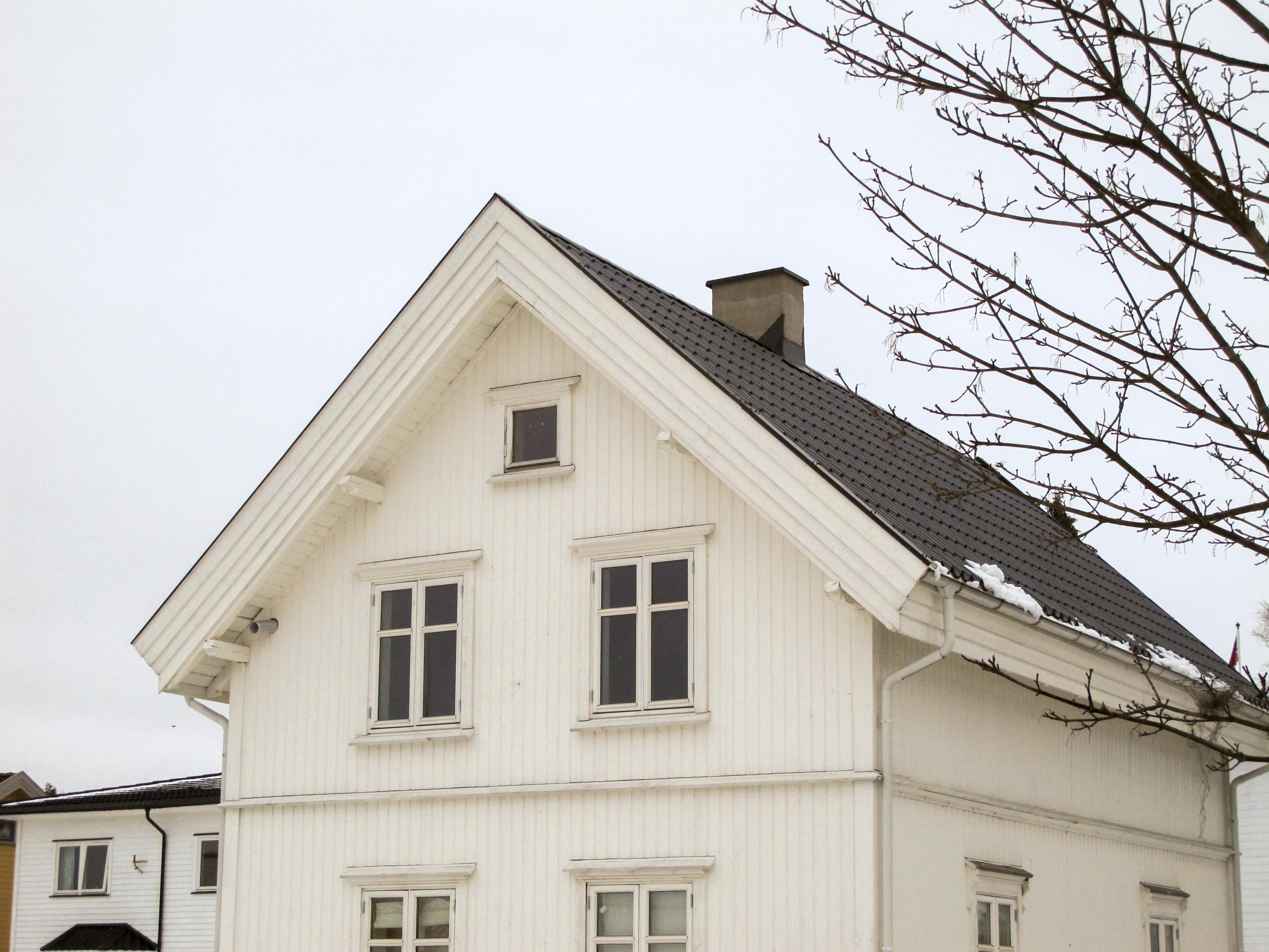 Ofte etterisoleres gamle hus utvendig - noe som fører til uheldige endringer i detaljering og proporsjoner. Her ser vi at taket har blitt etterisolert og vindskiene har blitt betydelig bredere, noe som gir huset et noe merkelig uttrykk, som om det har fått en ekstra tykk hatt tredd ned over bygningen. Foto: KM Frøyset