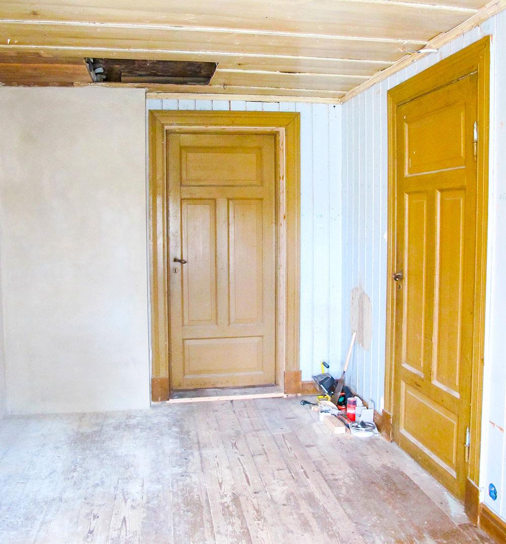 Dør til svalgang (t.h) og stue har gammel maling. På veggen ses spor etter utslagsvasken. Blåmalingen er bevart på to vegger. Nymurt, kopiert, brannmur i tegl med kalkmørtel.