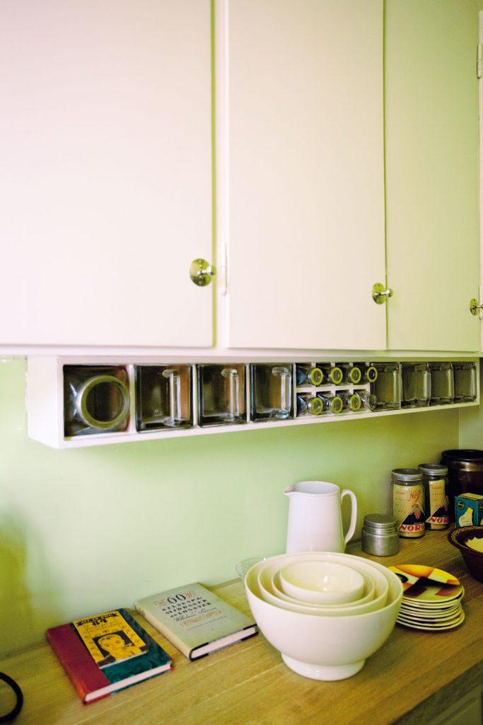 Detalj av innredning og kjøkkenbenk i Evelyn Bergs leilighet. Spiserisett i glass er montert under hyllene slik at beboeren enkelt kunne nå det hun hadde behov for.