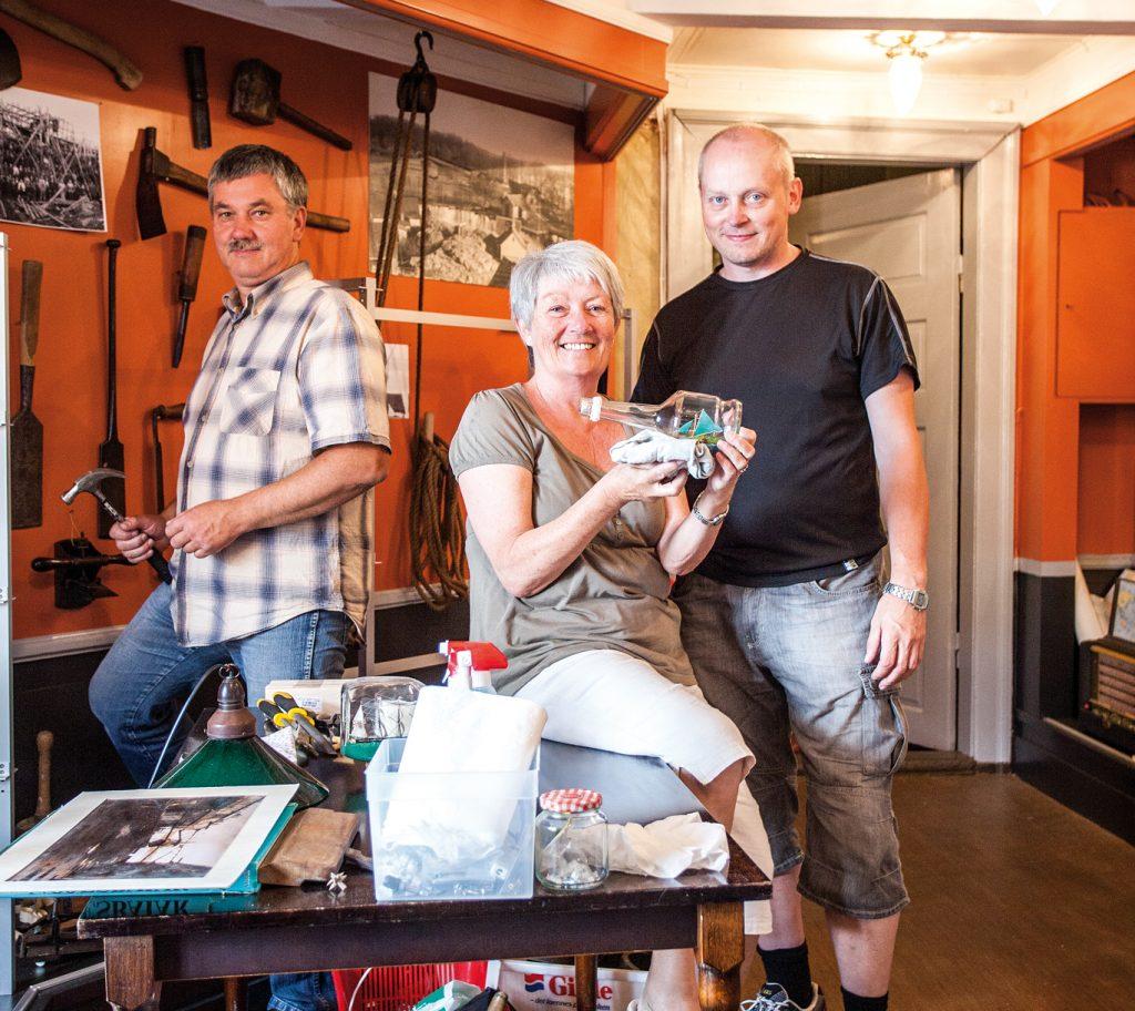 Fra venstre: Styremedlemmene Ole Ugland, Karin Kärrman (daglig leder) og Jan Fredrik Steine i ferd med å montere utstillingen av 655 flaskebåter som er donert til museet. Samlingen er nå notert i Guinness rekordbok!