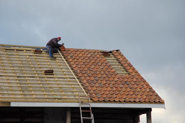 Gammel teglstein legges på taket, en lang lekte brukes som siktemål slik at radene blir rette og fine.