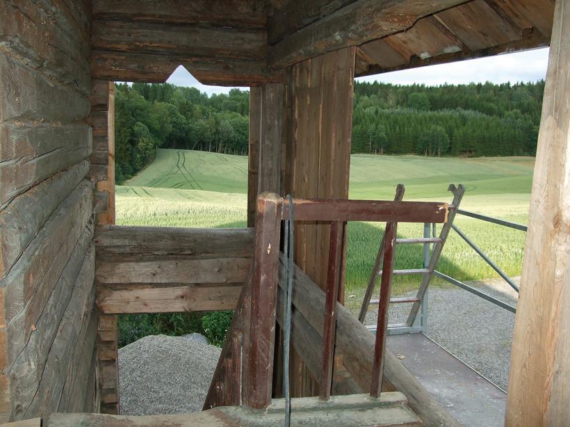 Utsikt mot skog og jorder fra svalgangen i andre etasje før den paneleres.