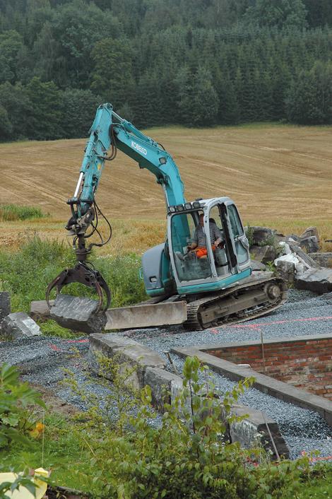 Store grunnmursstein legges på plass med gravemaskin.