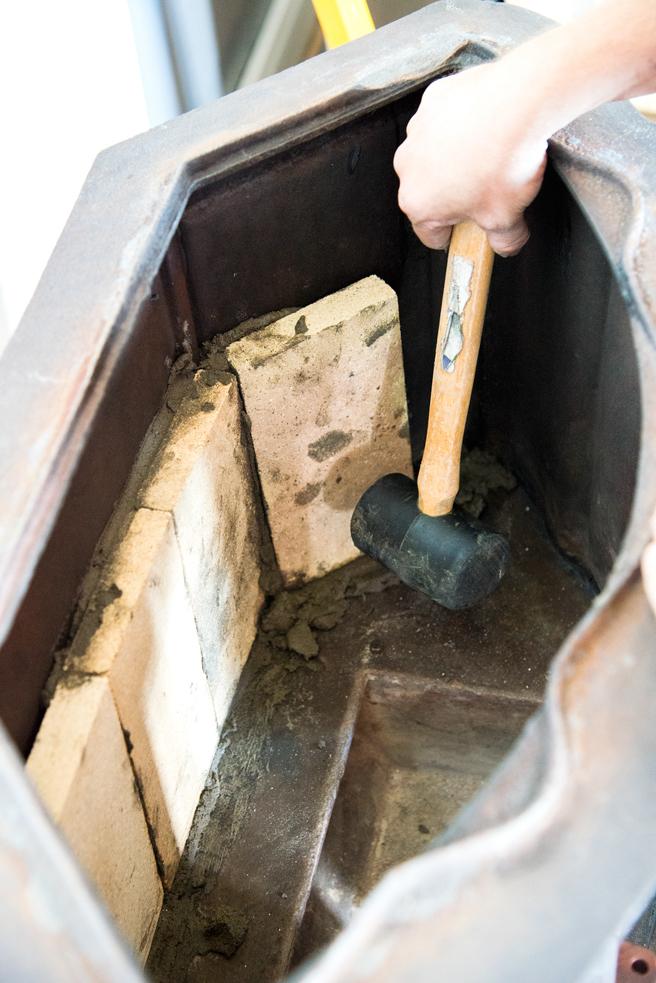 Jeg banker de ildfaste steinene forsiktig på plass med en gummihammer, slik at de sitter godt.