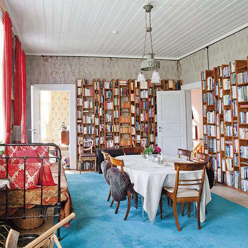En herlig miks av gammelt og nytt preger spisestua i andre etasje. Plassbygde, arkitekttegnede bokhyller rommer parets mange bøker. En gammel jernseng benyttes som divan. Legg merke til at tapetet i rommet er det opprinnelige. I enden av rommet skimtes det gule kontoret som ligger i det sydvestre tårnværelset.