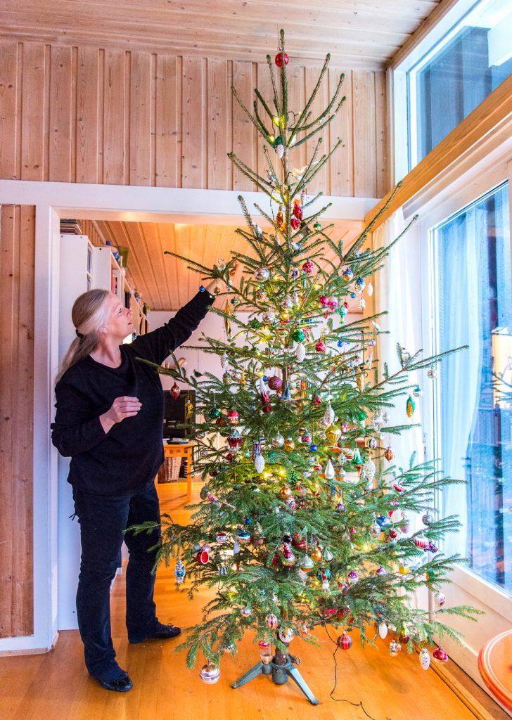 Familien bruker mange timer på å pynte treet, som rekker helt opp til taket.