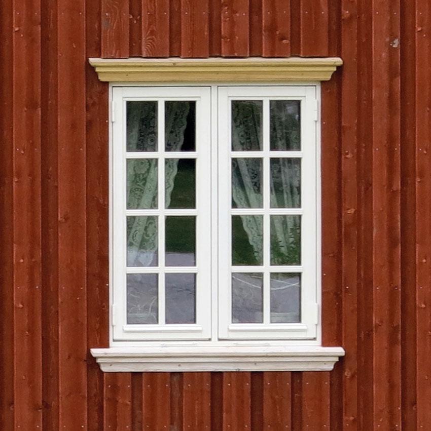 Denne masseproduserte vinduskopien har malte aluminiumsbeslag, enkle kraftige hengsler og falske sprosser. Legg merke til at lysåpningen blir endel mindre enn på originalen til venstre. Livløse glassruter og utenpåliggende kroker.