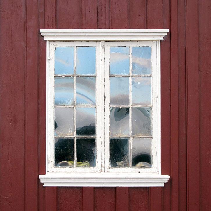 Et originalt vindu med slanke sprosser og vinkelbeslag. Her kan bare det ene vindusfaget åpnes. Legg merke til det vakre spillet i det håndlagede glasset.
