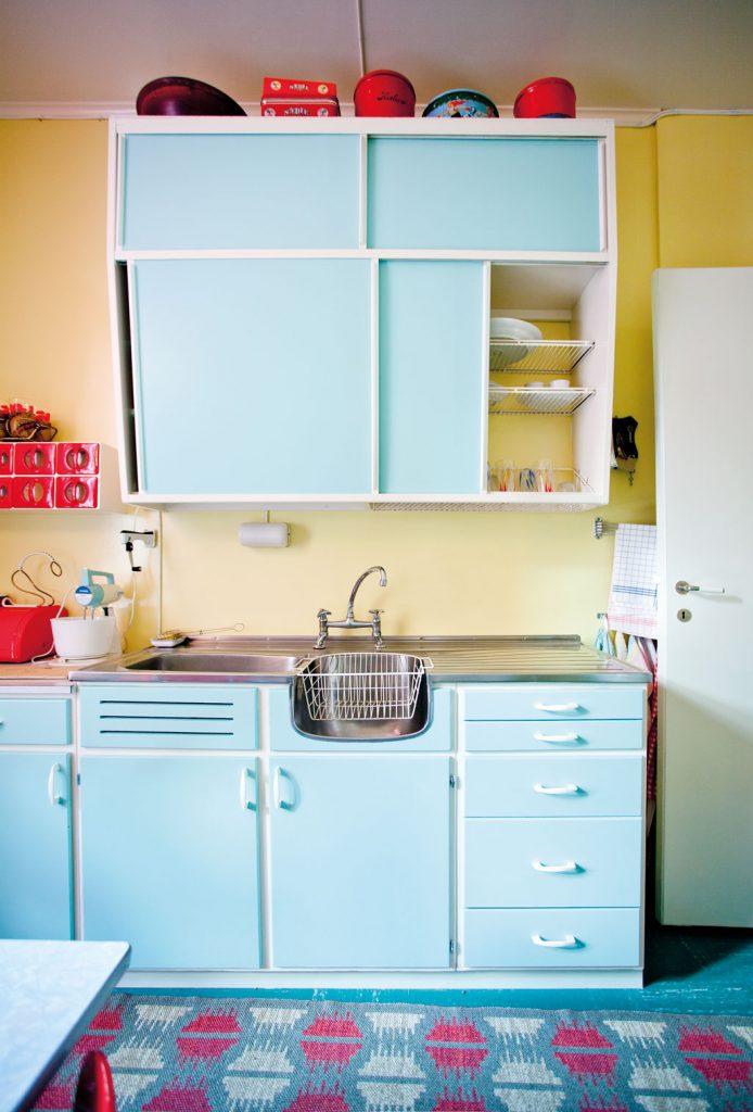 Kjøkkeninnredningen i leiligheten anno 1965 i Wessels gate på Norsk Folkemuseum er lyse blå og har plasthåndtak. Veggen er malt lysegul, «mimosa», noe som var svært populært på 1950- og 1960-tallet.